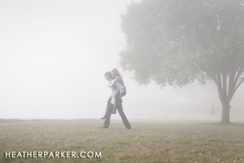 couple against beautiful surreal fog with a tree