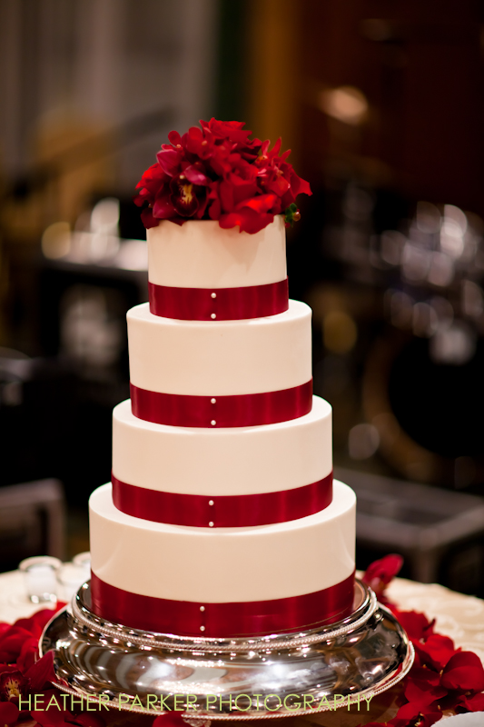 white and red wedding cake with ribbons and flowers