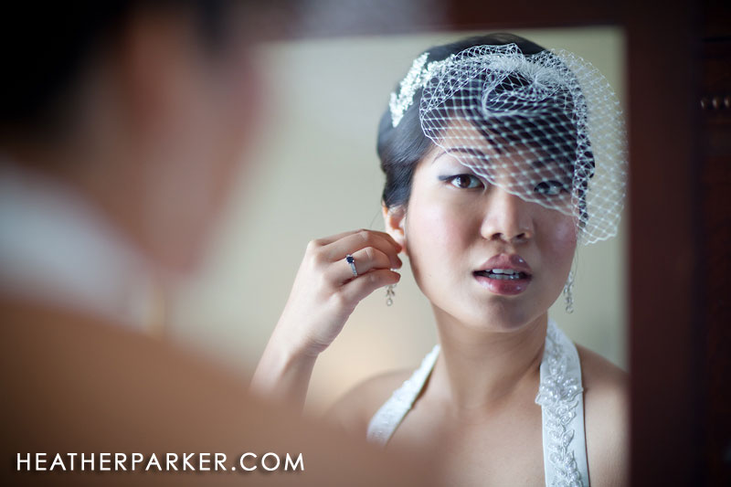 asian bride putting on earrings in a mirror on her wedding day