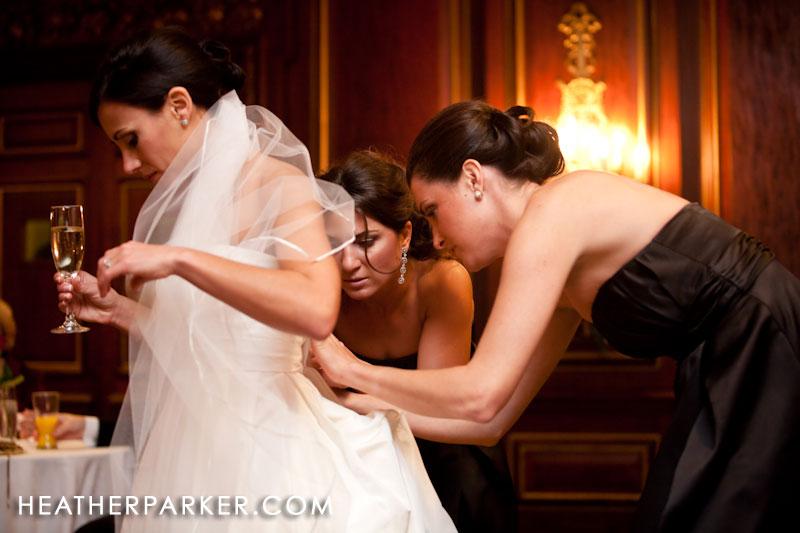 bride getting her amsale dress bustle